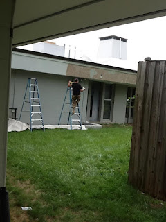 Worker painting the fascia band just under the roof of Aspen Hill library