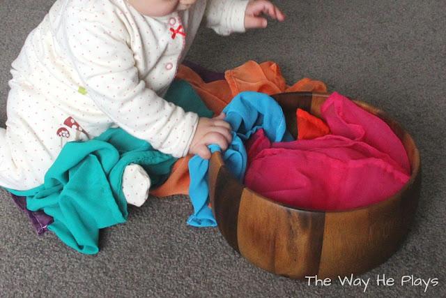 Baby exploring a treasure basket of play silks