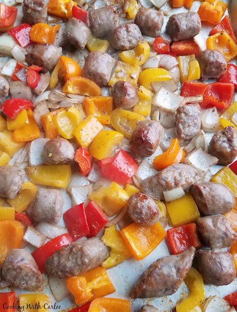 bits of browned Italian sausage and roasted onions and peppers on a sheet pan fresh from the oven