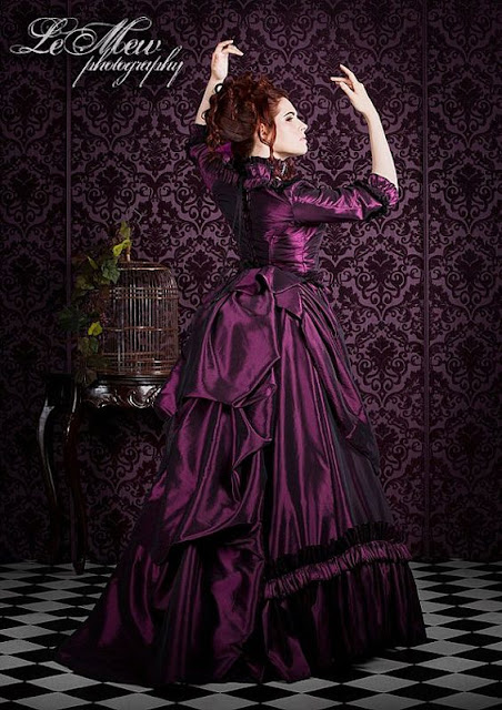 Woman wearing a plum purple Victorian ball gown. Perfect dress for Steampunk masquerade balls