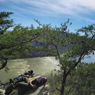 two hikers sleeping on rocks overlooking the potomac river on the appalachian trail