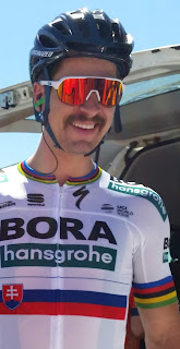 Portrait of a smiling Peter Sagan dressed in black helmet, sunglasses with white frames and orange reflective lens (they look like ski goggles); his white guernsey has World Champion stripes of blue, red, black and yellow on the collar and sleeve cuffs. The white, blue and red Slovakian flag is on the front below sponsorship logos which include the major team name sponsors BORA-Hansgrohe. In the background is the open tailgate of a van and clear blue sky.