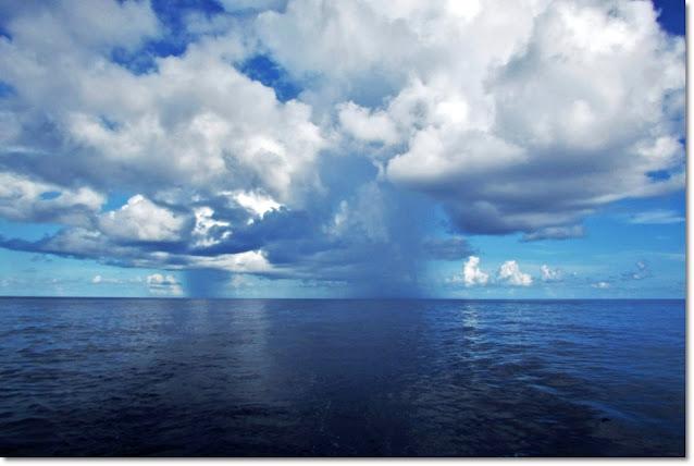 Rain falls from clouds onto a deep blue ocean horizon.
