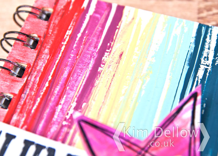 A close up of the texture of the painted rainbow notebook cover by Kim Dellow