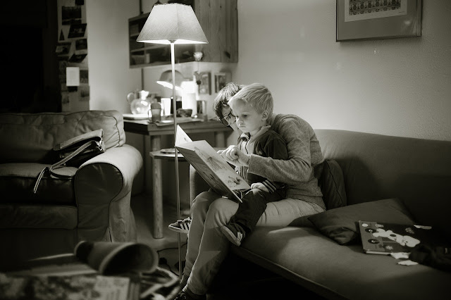 Son sitting on his mother's lap, both of them reading