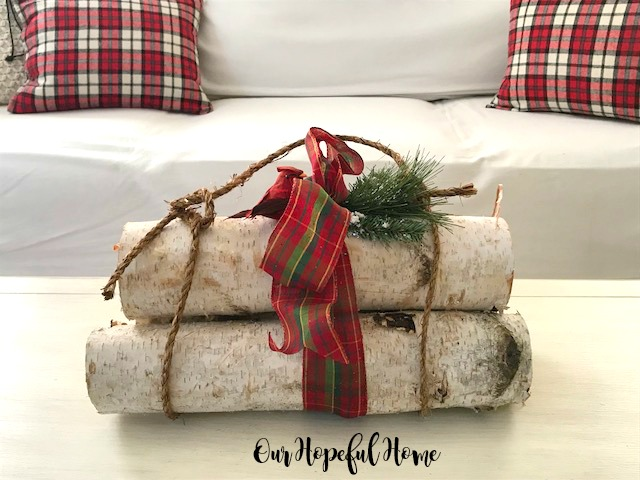 white birch logs stack red Christmas ribbon cardinal evergreens