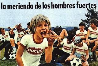 Fotografía de unos niños jugadores de fútbol merendando Nocilla untada en pan. Texto: La merienda de los hombres fuertes
