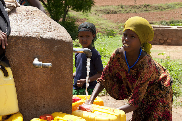 Local girls from Babile fill yellow water jugs at the area's main water source,  May 26, 2012 / Source: Wikimedia Commons