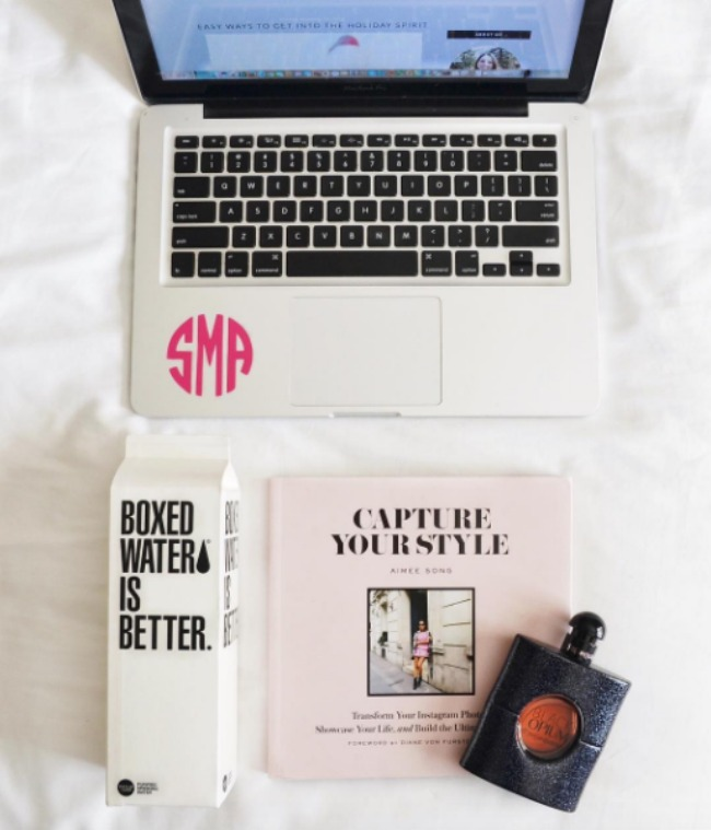 A flat lay of a computer with a monogram sticker, boxed water, Aimee Song of Song of Style's Capture Your Style coffee table book, and YSL black opium perfume.