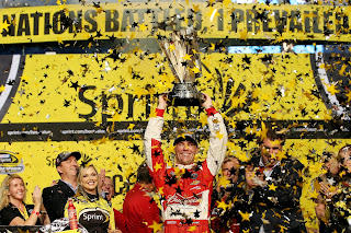 Kevin Harvick at the podium lifting the 2014 NASCAR Sprint Cup Series Championship trophy.