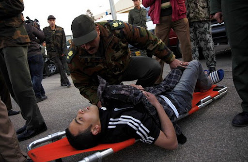 An Egyptian soldier checks on a wounded football Al-Ahly fan