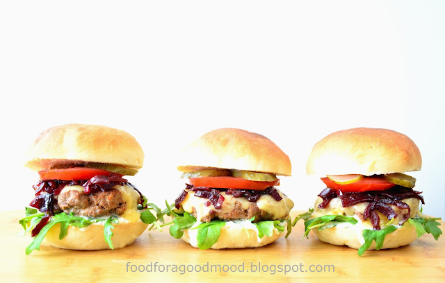 Nachodzą mnie czasem takie chwile, kiedy mam nieodpartą ochotę zatopić zęby w pysznym burgerze...  O! Na przykład takim, gdzie podstawą jest średnio mielona, soczysta wołowina, doprawiona kolendrą, imbirem i pikantnym ketchupem. Do tego: rukola, żółty ser oraz standardowo - pomidor i ogórek konserwowy. O wyśmienitym smaku decydują szczegóły: czosnkowy majonez i karmelizowana czerwona cebulka, które w wyrazisty sposób łączą wszystkie składniki w pyszną całość.
