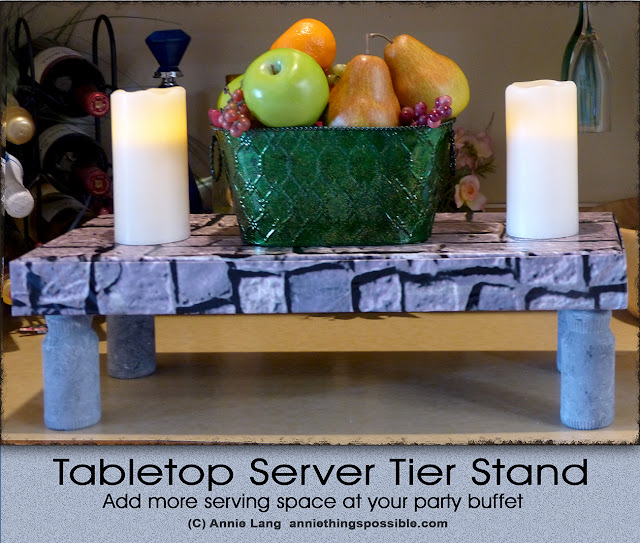 Make Annie Lang's medieval themed server stand from Sunny D bottles and a box