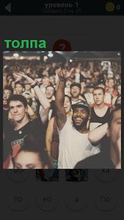 Большое количество людей в одном месте, толпа кричит и поднимает руки вверх