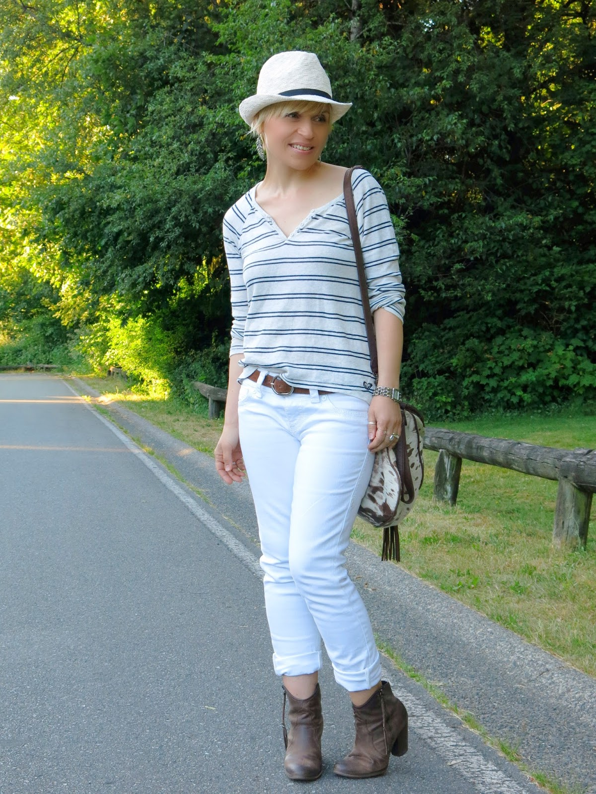 styling white jeans with a striped henley top, booties, and a fedora