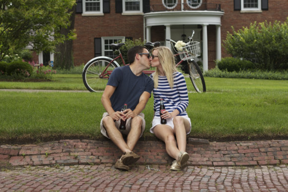 This happy engaged couple share a kiss on the grass in front of their tandem bike.