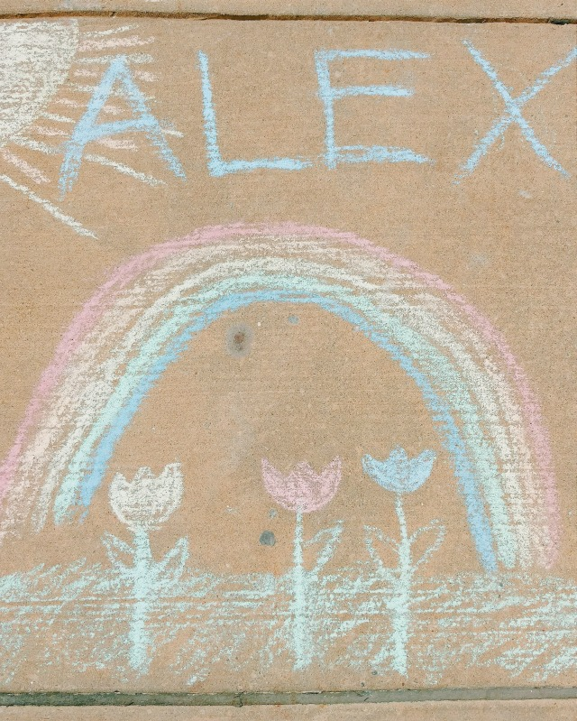 """Chalk drawing that says """"Alex"""" in the sky with a sun next to it, a rainbow, and tulips underneath."""