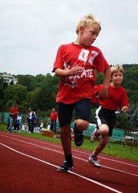 Kinder laufen auf einer Tartanbahn