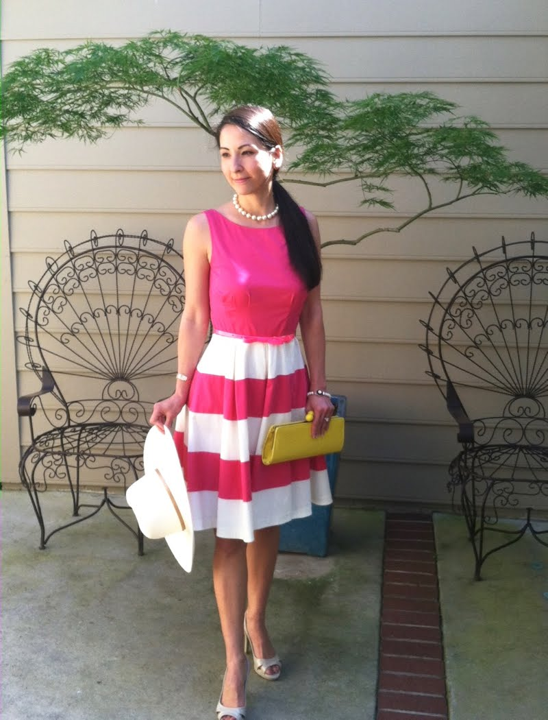 Wearing a line dress with pink bodice and pink and white striped skirt. Short strand of white pearls, beige heels, a beige floppy hat and a yellow clutch.