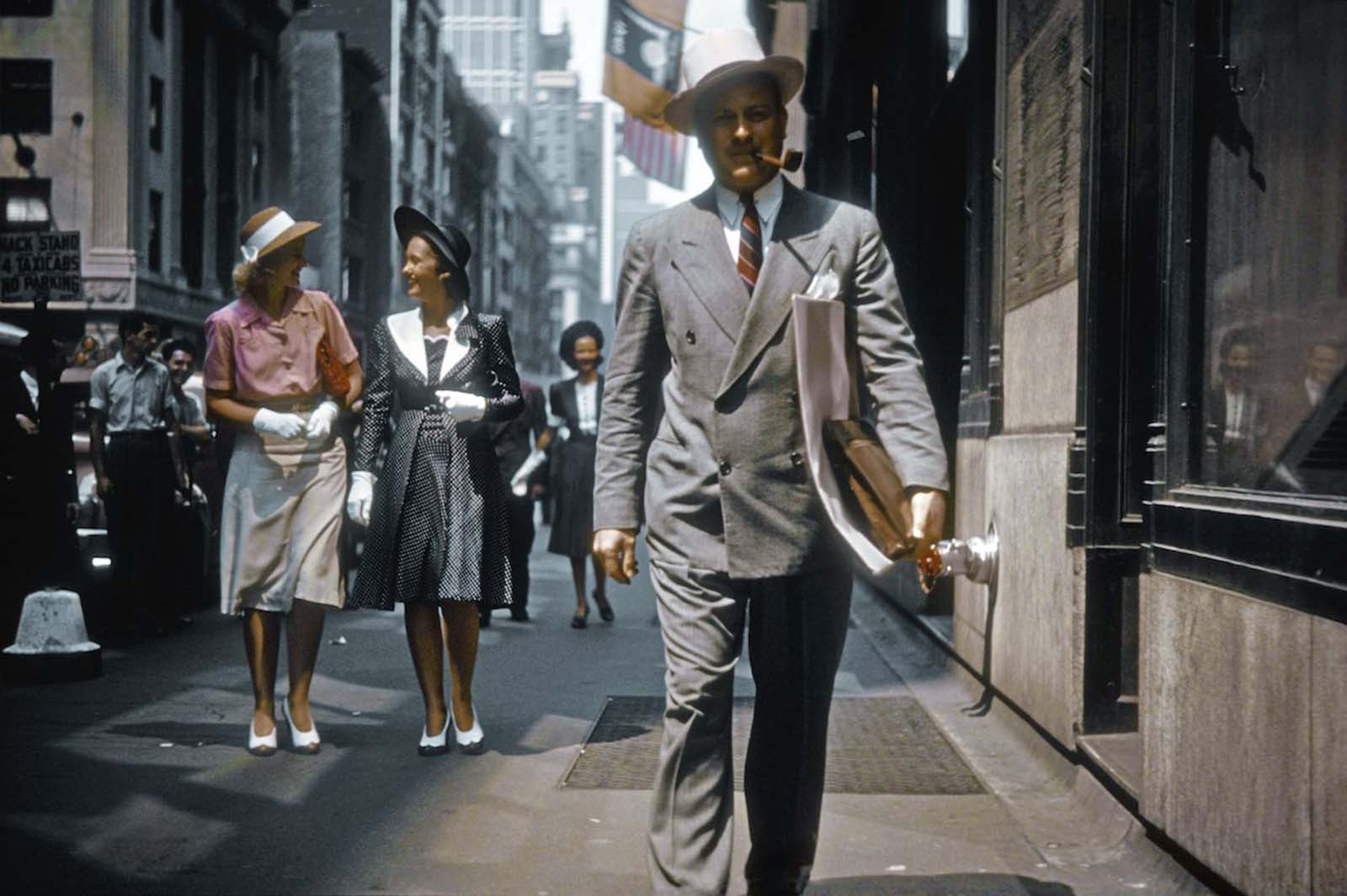 A man walks down Madison Avenue on a clear, warm day. Behind him, three women are wearing white gloves.