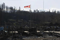 A Canadian flag flies over damage caused by a wildfire, which prompted the mass evacuation of over 88,000 people, in Fort McMurray, Alberta, Canada on May 14, 2016. (Credit: Chris Schwarz/Government of Alberta/Handout via Reuters) Click to Enlarge.