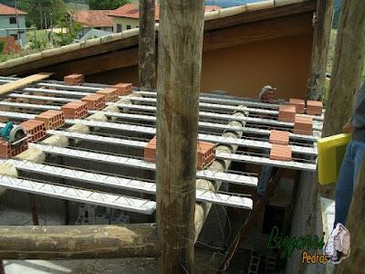 Detalhe da armação da laje do piso em cima das vigas de madeira de eucalipto tratado com os pilares de madeira com a alvenaria de bloco de cimento em construção de sala de estar com a suíte superior em construção rústica no sul de Minas Gerais-MG.