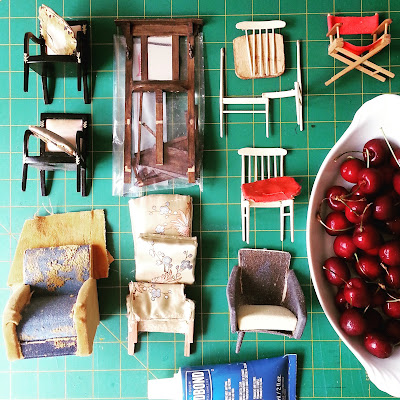Selection of broken one-twelfth scale miniature chairs (and a hall stand) laid out on a cutting mat with a tube of glue and a bowl of cherries.