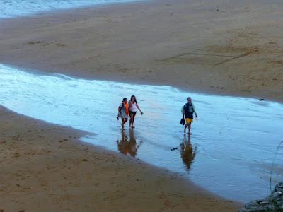 Tres figuras abandonan la playa sobre un reguero plateado