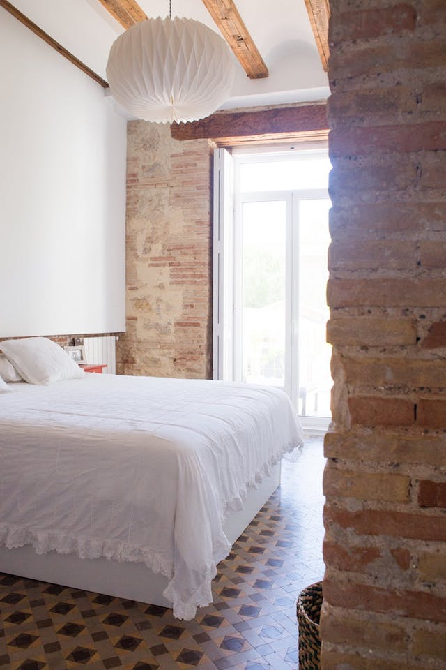 dormitorio con pared de mamposteria y vigas de madera