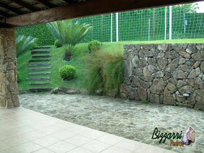 Construção do muro de pedra bruta com o piso de pedra, a escada de dormente de madeira com a execução do paisagismo em residência em Mairiporã-SP.