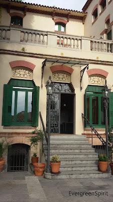 Entrada de un edificio de tipo modernista donde se puede apreciar las escaleras que llevan a la puerta principal que está abierta.