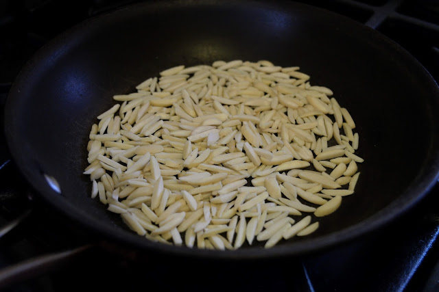 Almond slivers being toasted in a dry pan.