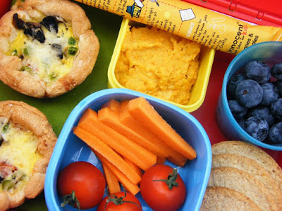 a vegetarian kids lunchbox including baby egg pies, oatcakes, carrots and cherry tomatoes