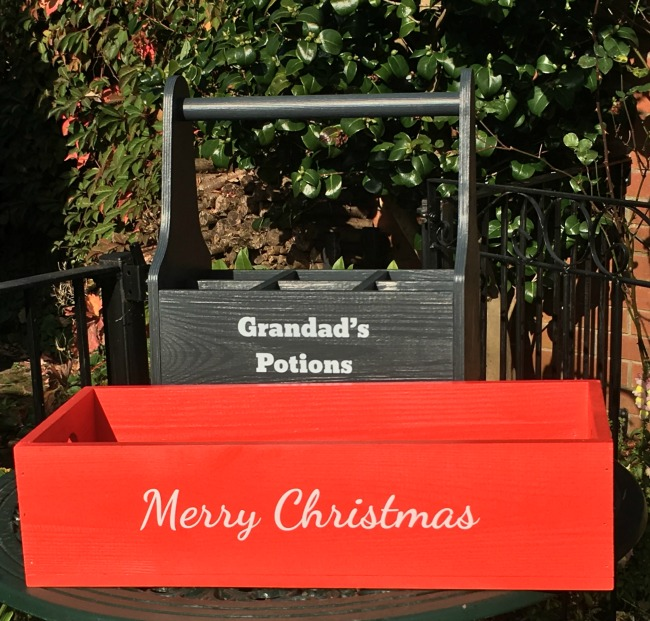 Plantabox-personalised-wooden-apple-crate-image-of-empty-red-table-centrepiece-with-white-text-Merry-Christmas-and-grey-kitchen-caddy-with-text-Grandads-potions