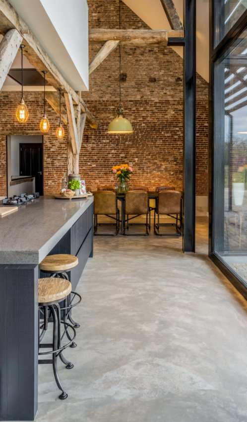Beautiful kitchen with exposed brick wall in dramatic barn conversion