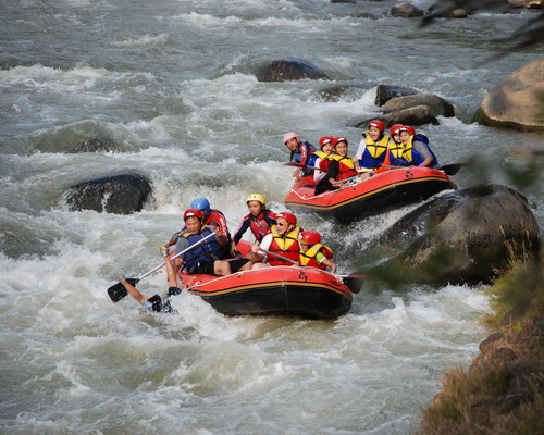 Tinuku.com Travel Progo River rafting trips enjoy class 5 sensation riding boat on big stone and view Menoreh mountains