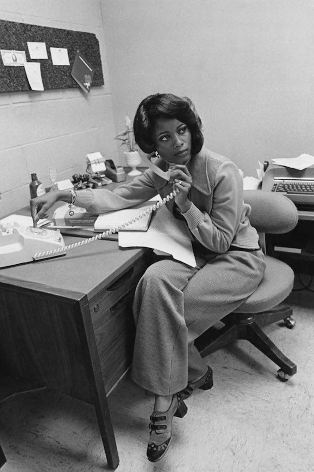 An African-American office worker takes a phone call. She wears a loose-fitting cardigan with a wide collar and wide, loose pants. Her shoes are unusually patterned. She wears a bracelet and ring, and her hair is lightly styled. 1975.