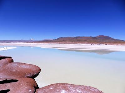 Piedras coloradas sobre la laguna Aguas Calientes bajo un cielo azul intenso