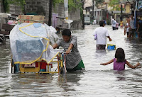 A man pushes his bicycle cart through waist-deep flooding caused by typhoon Linfa at Longos town in Malabon city, north of Manila July 6, 2015. (Credit: REUTERS/Romeo Ranoco) Click to Enlarge.