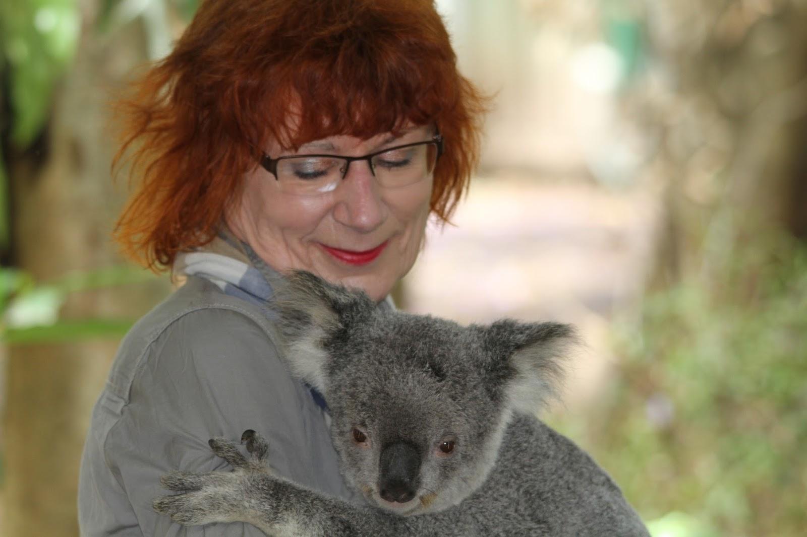A woman holding a koala.