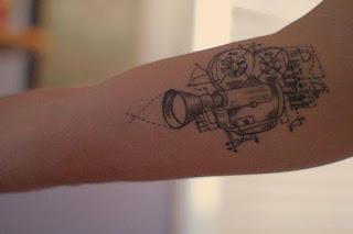 Tatuaje cámara de cine en antebrazo