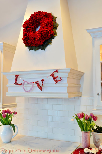White kitchen hood with Love banner and red wreath on it