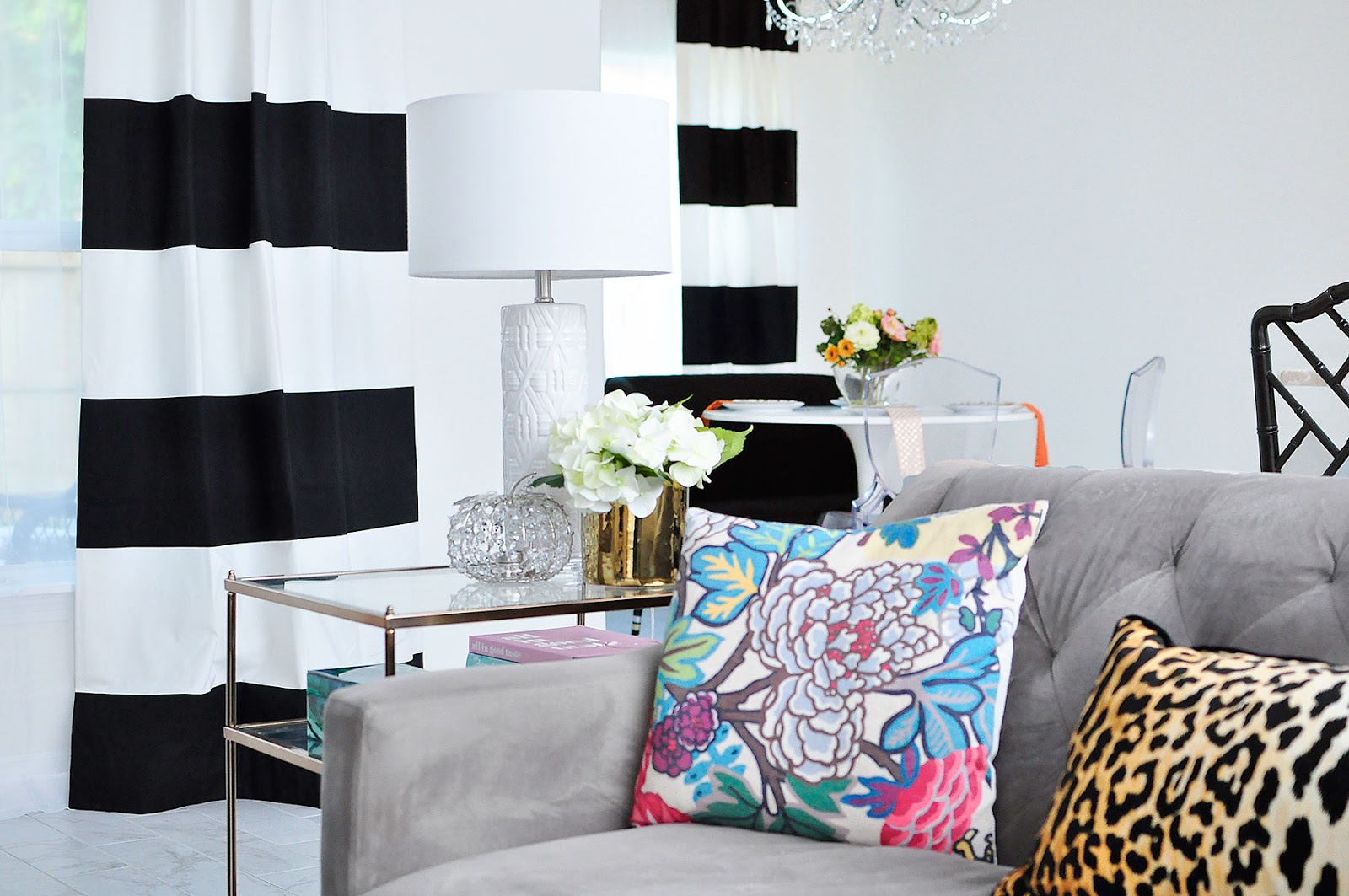 Black and white curtains in a living room with a gray sofa and colorful chinoiserie accents.