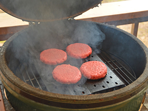 Grilling burger patties on GrillGrates in a kamado grill, such as Kamado Joe, Big Green Egg, Primo