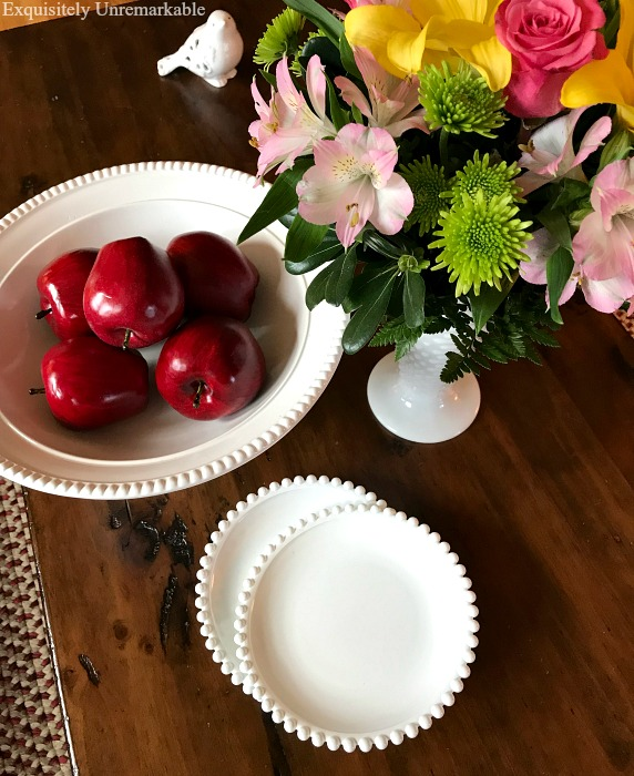 Faux white milk glass dishes, bowl filled with apples and a white flower filled vase on coffee table