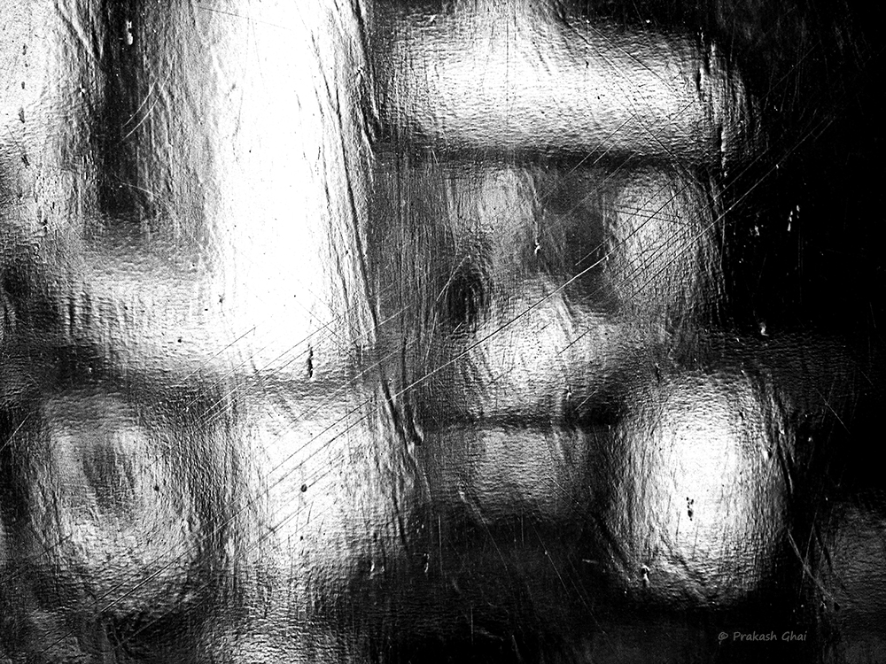 A Black and white Minimalist Photo of Blurred abstract shapes behind a plastic curtain.