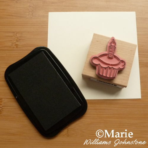 Inking a cupcake birthday stamp with black