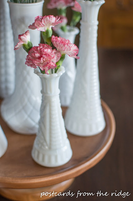 Such a sweet little milk glass vase with carnations. Nice centerpiece.
