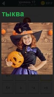 Девочка с тыквой в руках и шляпой на голове. Тыква вырезана для хеллоуина