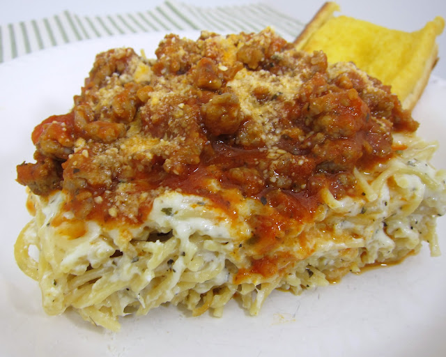 Baked Spasanga - lasagna and spaghetti in one! Baked pasta with mozzarella, ricotta, sour cream, half-and-half and parmesan. Topped with a quick meat sauce. SOOO good! Makes a great freezer meal too. Perfect for a potluck!